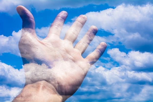 Eine menschliche hand und der blaue himmel.