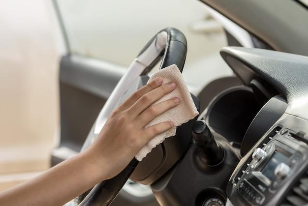 Eine menschliche hand wischt das lenkrad eines autos mit einem lappen ab. waschen sie ein verschmutztes lenkrad mit einem reiniger.