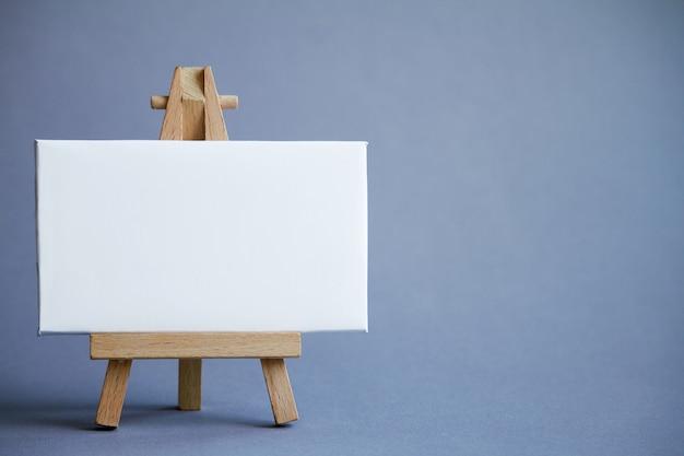 Eine miniatur staffelei mit einer weißen tafel zum schreiben, zeiger auf weiße fläche