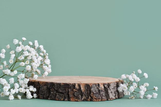Eine minimalistische szene eines gefällten baumes liegt mit blumen auf einem natürlichen hintergrund.