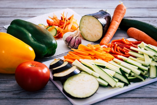 Eine mischung aus frischem filetgemüse, zucchini, karotten, paprika und auberginen, fertig zum kochen und für brötchen