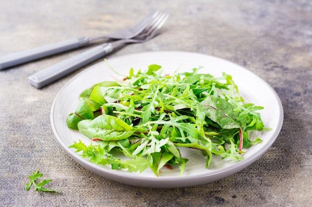 Eine mischung aus frischem rucola, mangold und mizun-blättern auf einem teller und gabeln auf dem tisch. gesundes essen