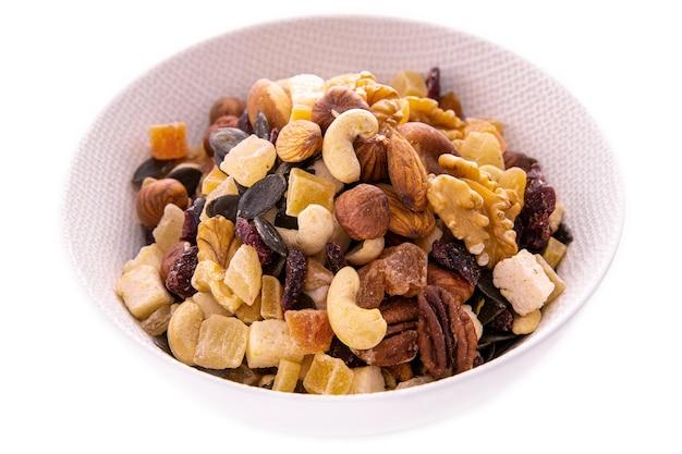 Eine mischung aus gehackten trockenfrüchten und beeren, nüssen in einem weißen teller auf weißem hintergrund. isolierte artikel und produkte.