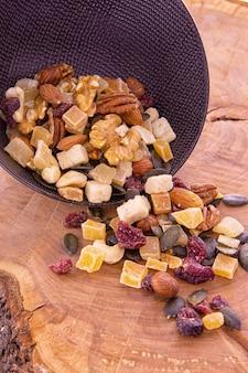 Eine mischung aus geschnittenen getrockneten früchten und beeren, nüssen, die aus einer dunklen tasse auf einem holz verschüttet wurden