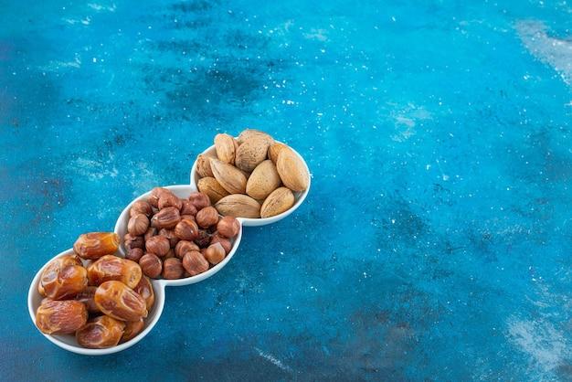 Eine mischung aus nüssen in einer schüssel auf der blauen oberfläche