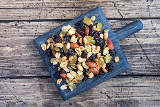 Eine mischung aus nüssen und trockenfrüchten auf einem schneidebrett aus holz, rustikaler hintergrund. konzept der gesunden ernährung.