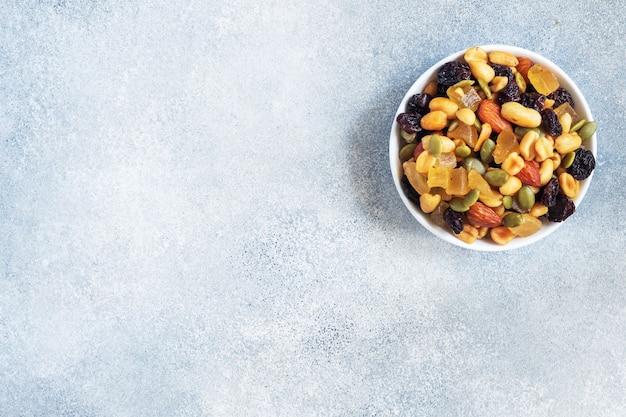 Eine mischung aus nüssen und trockenfrüchten in einer keramikplatte auf grauem betonhintergrund. konzept der gesunden ernährung. platz kopieren