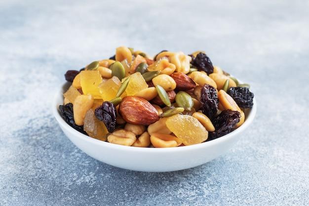 Eine mischung aus nüssen und trockenfrüchten in einer keramikplatte auf grauem betonhintergrund. konzept der gesunden ernährung.