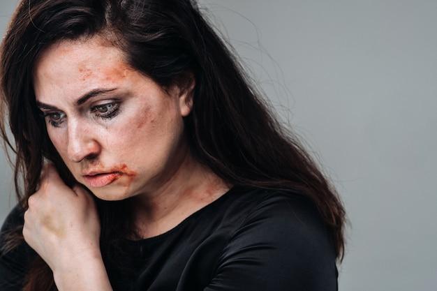 Eine misshandelte frau in schwarzen kleidern auf einem isolierten grauen hintergrund. gewalt gegen frauen