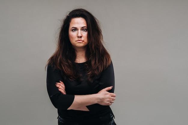 Eine misshandelte frau in schwarzen kleidern auf einem isolierten grauen hintergrund. gewalt gegen frauen.