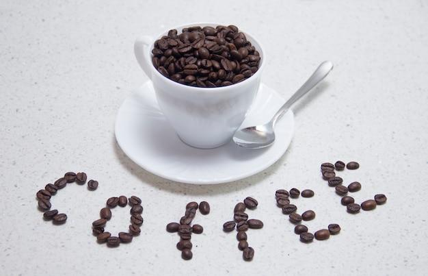 Eine mit gerösteten kaffeebohnen geschriebene inschrift auf dem tisch