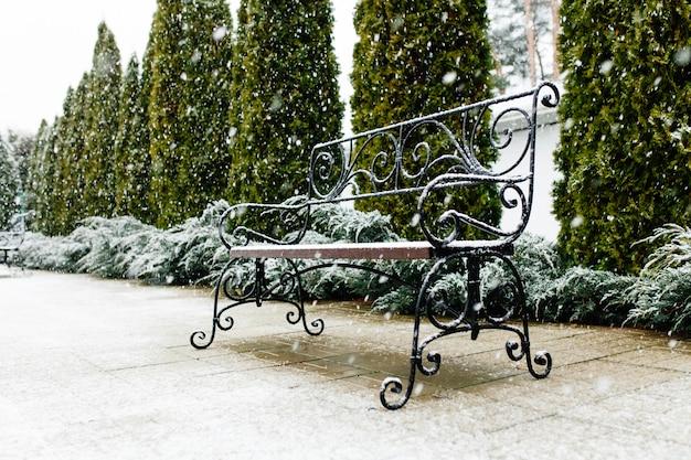 Eine mit schnee bedeckte parkbank. schnee, schöner schnee, schönes wetter
