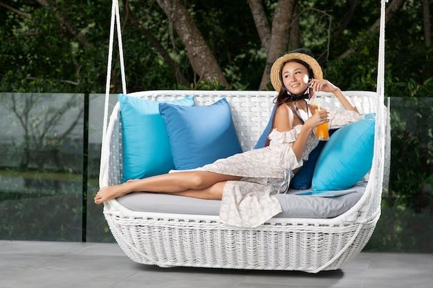 Eine modefrau im strohhut, die tropencocktail der frischen frucht mit orange im hohen glas hält, das auf sofa gegen tropischen hintergrund sitzt