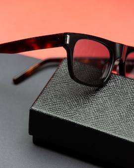 Eine moderne schwarze sonnenbrille der vorderansicht auf der rosa-dunklen