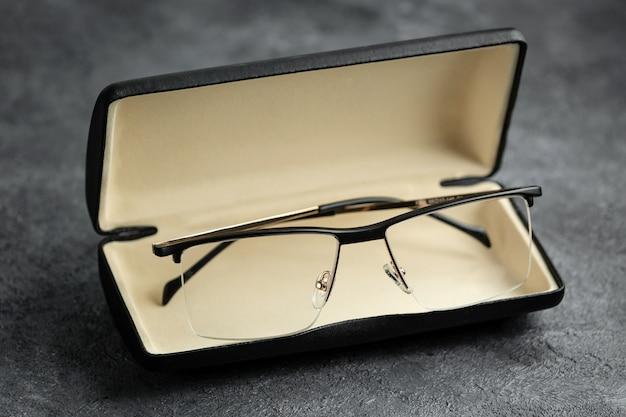 Eine moderne sonnenbrille der vorderansicht modern innerhalb der kleinen box auf dem grauen schreibtisch isolierte vision brille eleganz