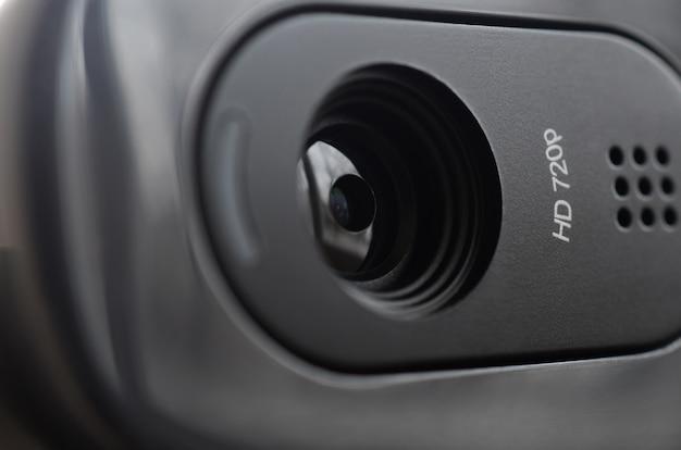Eine moderne webkamera ist auf dem gehäuse eines flachbildschirms installiert. gerät zur videokommunikation und aufzeichnung von qualitativ hochwertigem video