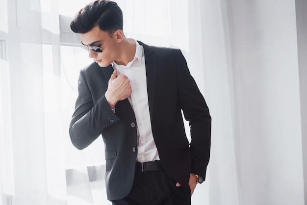Eine modische frisur sticht heraus. porträt des jungen stilvollen mannes in der klassischen geschäftskleidung, die im weißen raum steht.