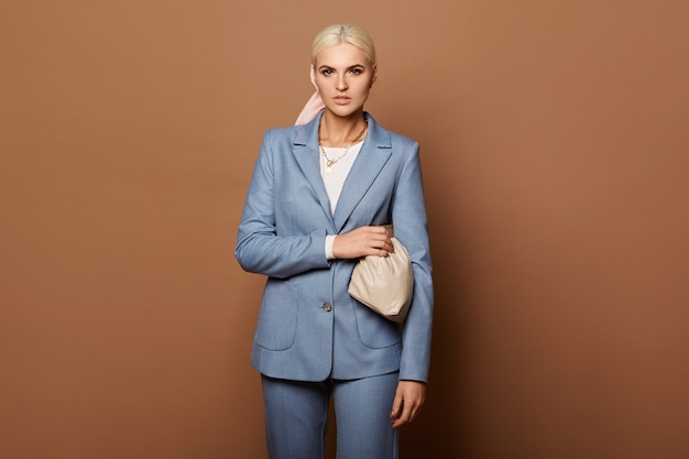 Eine modische junge frau mit perfektem blondem haar in einem eleganten blauen anzug auf dem beigen hintergrund, lokalisiert mit kopienraum. konzept der geschäftsmode und schönheit