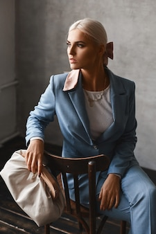 Eine modische junge frau mit perfektem blondem haar in einem eleganten blauen anzug, der im studio aufwirft