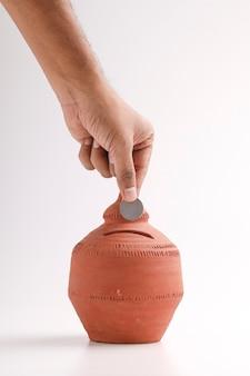 Eine münze in eine sparbüchse aus ton stecken: investitionen, pensionskasse und bankkonzept