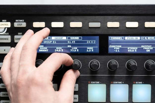 Eine musikerhand passt den klang mit dem knopf an, mischt elektronische musik