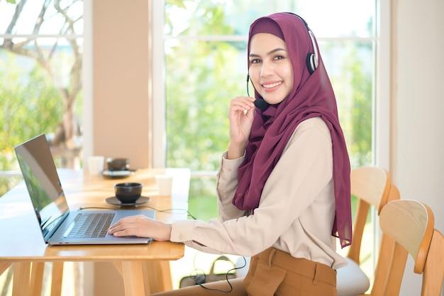 Eine muslimische betreiberfrau im headset unter verwendung des computer, der kundenanruf im büro, kundendienstkonzept beantwortet