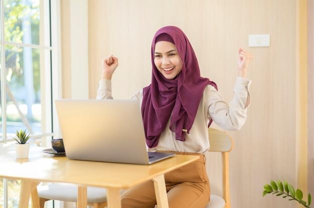 Eine muslimische geschäftsfrau, die hijab trägt, der mit ihrem laptop im café arbeitet