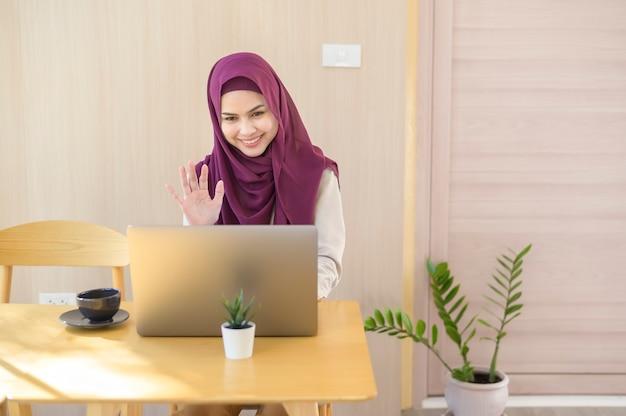 Eine muslimische geschäftsfrau in kopfhörern, die webinar auf laptop beobachten und einen videoanruf am arbeitsplatz machen