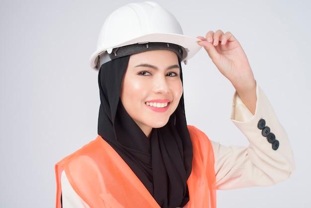 Eine muslimische ingenieurin, die einen schutzhelm über weißem hintergrundstudio trägt?