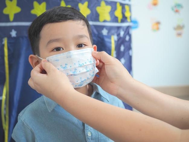 Eine mutter, die eine schutzmaske für ihr kind trägt, um sich vor viren oder kranken menschen zu schützen