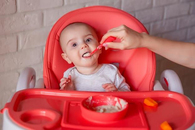 Eine mutter füttert ihr unzufriedenes kind mit einem löffel