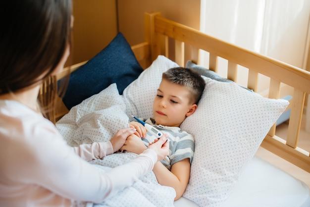 Eine mutter kümmert sich um ihr kind, das fieber und fieber hat. krankheit und gesundheitswesen.