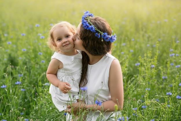 Eine mutter küsst ihre tochter in einem kornblumenfeld bei sonnenuntergang