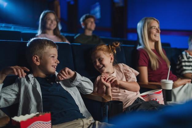 Eine mutter mit glücklichen kleinen kindern im kino, die filme guckt und lacht.