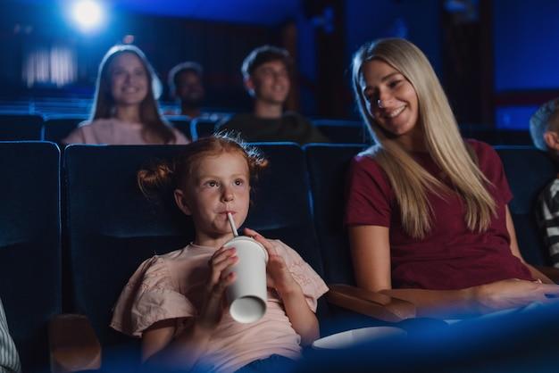 Eine mutter mit glücklichen kleinen kindern im kino, die filme guckt und mit einem strohhalm trinkt.