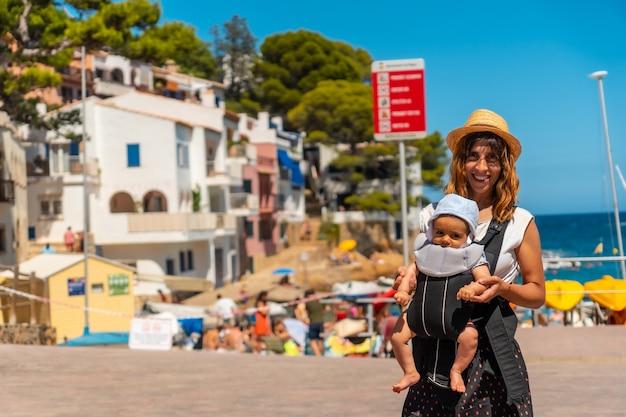 Eine mutter mit ihrem baby am strand von sa tuna an der küste von begur im sommer, girona an der costa brava von katalonien im mittelmeer