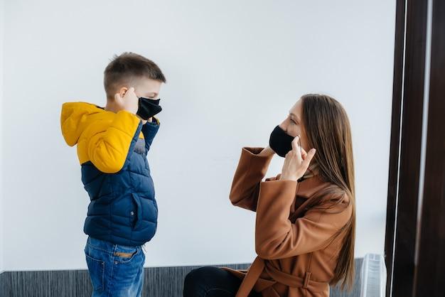 Eine mutter mit ihrem kind steht während der quarantäne in einer maske