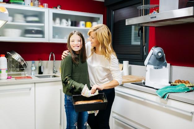 Eine mutter mit ihrer tochter in der küche zu hause bereitet gemeinsam als familie einen kuchen zu