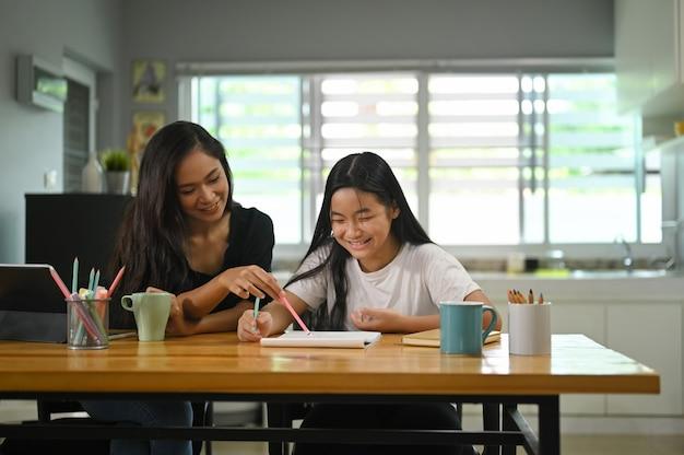 Eine mutter sitzt mit ihrer tochter zusammen und unterrichtet ihre hausaufgaben am hölzernen schreibtisch.