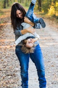 Eine mutter spielt mit kleinkind in einem wald Premium Fotos