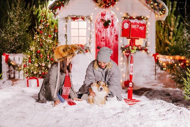 Eine mutter und eine tochter, die mit corgi hund im schnee spielen