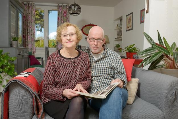 Eine mutter und ihr erwachsener sohn, die ein fotoalbum auf einem sofa betrachten