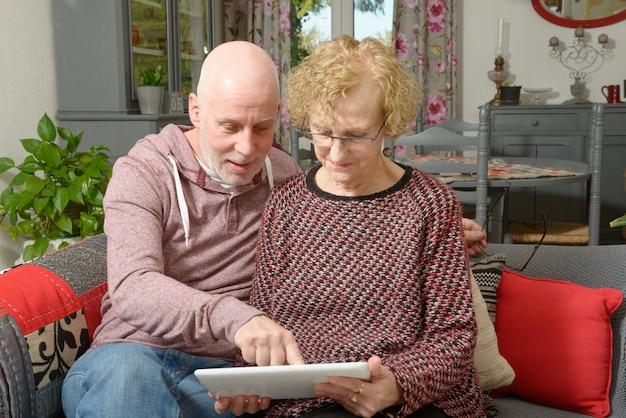 Eine mutter und ihr erwachsener sohn, die eine digitale tablette auf einem sofa betrachten