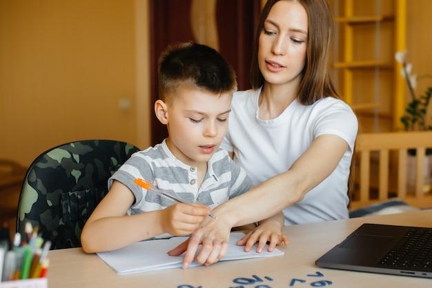 Eine mutter und ihr kind lernen zu hause vor dem computer fernunterricht. bleib zu hause und trainiere.