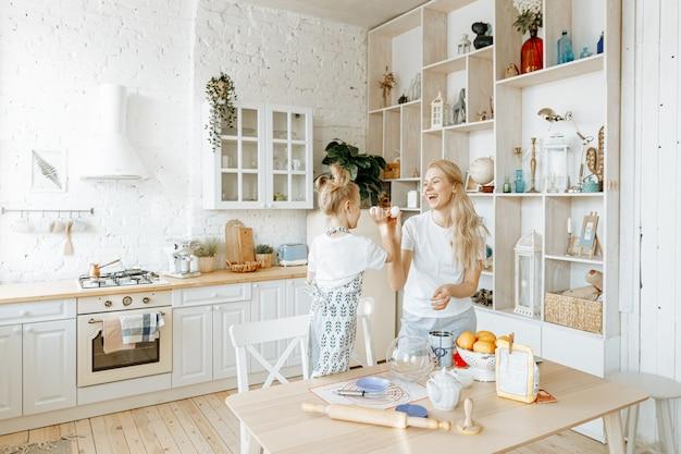 Eine mutter und ihre kleine tochter bereiten gemeinsam in ihrer küche zu hause backteig zu.
