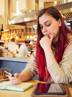 Eine nachdenkliche frau mit roten haaren arbeitet fern in einem café und schreibt in ein tagebuch