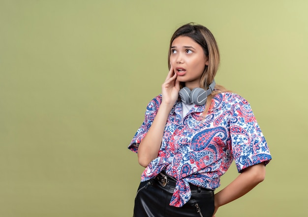 Eine nachdenkliche junge frau, die ein hemd mit paisley-aufdruck in kopfhörern trägt und mit der hand auf gesicht denkt, während sie aufschaut
