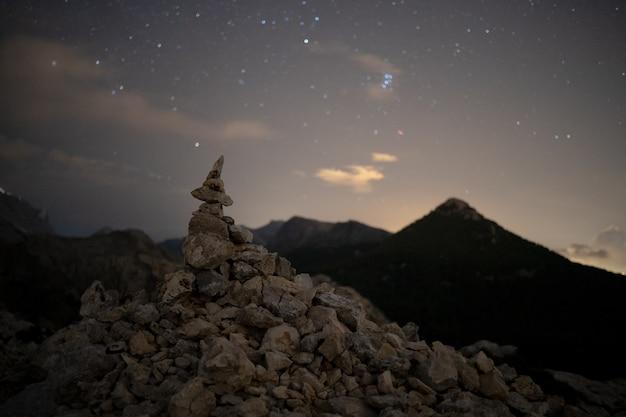Eine nachtaufnahme eines meilensteins, der den berg ofre auf mallorca nachahmt