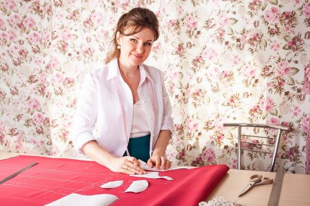 Eine näherin in ihrem eigenen atelier macht ein muster