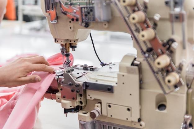 Eine näherin näht kleidung an der nähmaschine. textilwerkstatt. nahaufnahme
